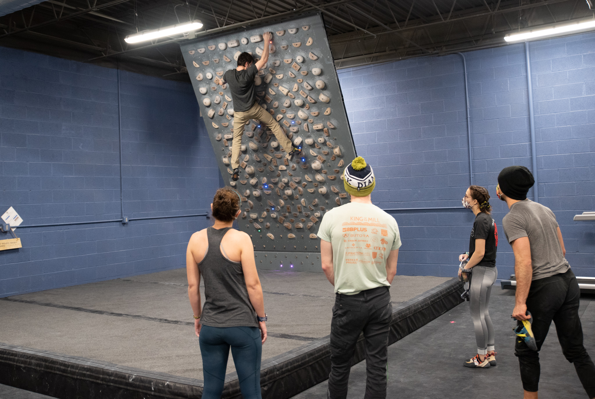 Man Climbing On The Tension Board While His Friends Cheer Him On