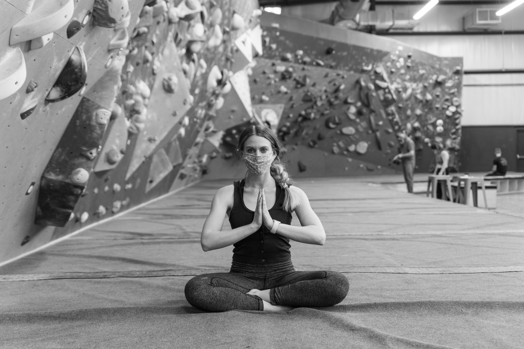 Yoga instructor sitting cross-legged with her hands to her heart